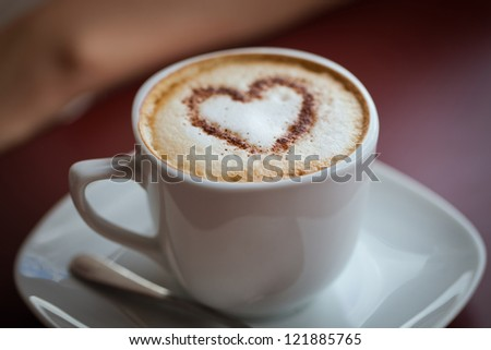 cup of cappuccino coffee, chocolate heart on top - stock photo