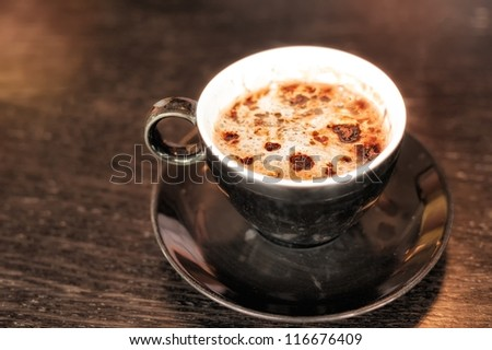 Cup of cappuccino coffee decorated with chocolate on dark table - stock photo