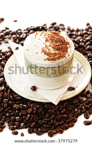 Cup of cappuccino coffee on beans over light background