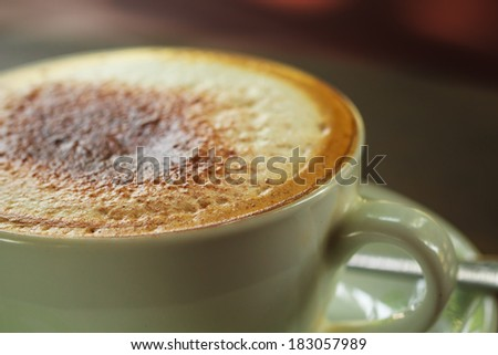 Cup of cappuccino coffee on wood table - stock photo