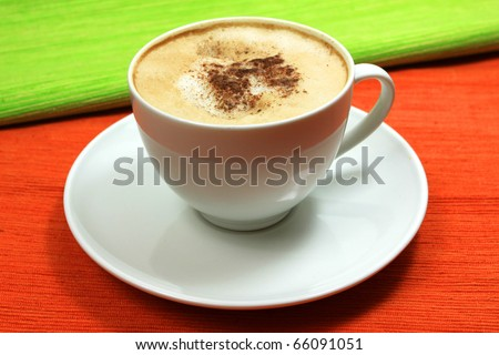 Cup of cappuccino coffee over orange and green background - stock photo