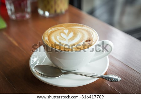 cup of cappuccino, cup of coffee, cup of coffee on brown wooden table - stock photo