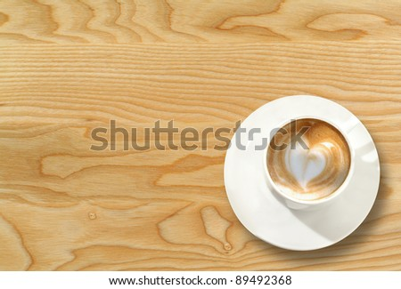 Cup of cappuccino on wooden table. - stock photo