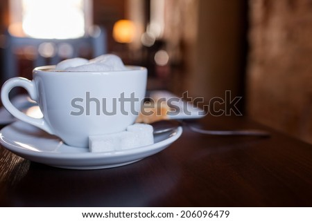 Cup of Cappuccino on wooden table. Cafe - stock photo