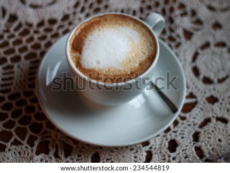 Cup of cappuccino served on table with lace tablecloth