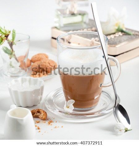Cup of cappuccino set with cookies, cherry blossoms and perfume. Light and airy photo. Beautiful spring time and ladies fashion concept. - stock photo