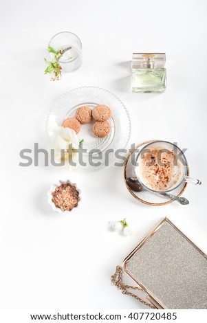 Cup of cappuccino set with cookies, cherry blossoms and perfume, overview. Light and airy photo, instagram style. Beautiful spring time and ladies fashion concept.