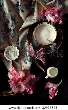 Cup of cappuccino set with pink flowers, natural lighting, dark style photo, overview. Romantic background with retro filter effect - stock photo