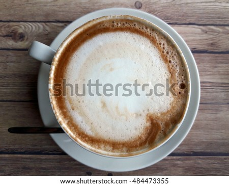 Cup of cappuccino top view on wooden table