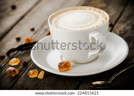 cup of cappuccino, vanilla stcks, anise stars, coffee bans, sugar and old metallic spoon on old wooden table - stock photo
