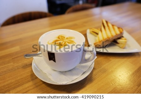 Cup of cappuccino with blur coffee shop background and sandwich - stock photo