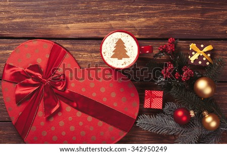 Cup of cappuccino with Christmas tree shape and gifts with pine tree branch on wooden background
