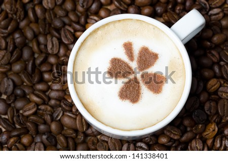 cup of cappuccino with cinnamon pattern on a background of coffee beans, horizontal close-up - stock photo