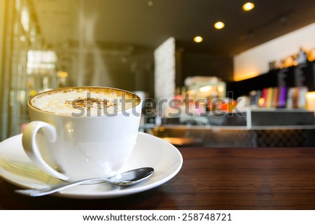 Cup of cappuccino with coffee shop background  - stock photo