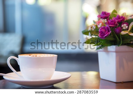 Cup of cappuccino with flower bouquet in coffee shop  - stock photo