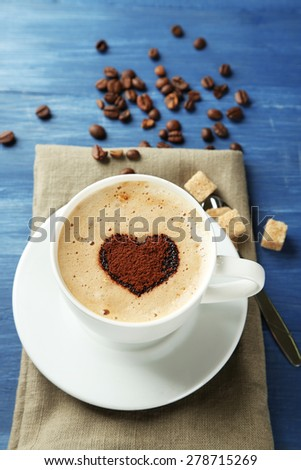 Cup of cappuccino with heart of cocoa on wooden table - stock photo