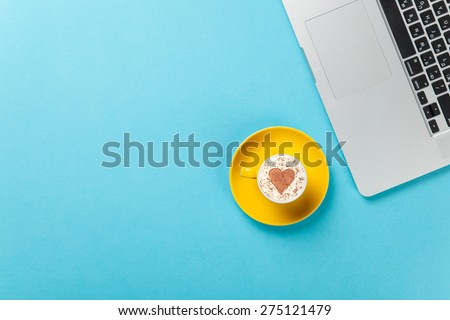 Cup of cappuccino with heart shape and laptop on blue background. - stock photo
