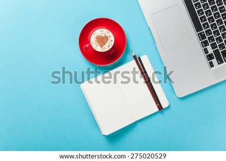 Cup of cappuccino with heart shape and laptop with note on blue background. - stock photo