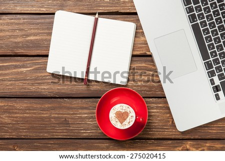 Cup of cappuccino with heart shape and notebook near laptop on wooden table. - stock photo