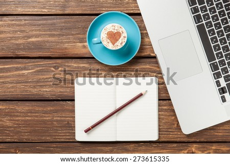 Cup of cappuccino with heart shape and notebook with pencil near laptop on wooden table. - stock photo