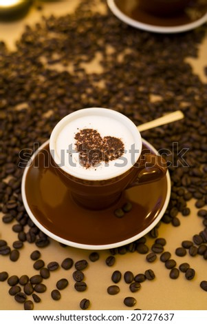 cup of cappuccino with heart shape on froth, coffeebeans around - stock photo