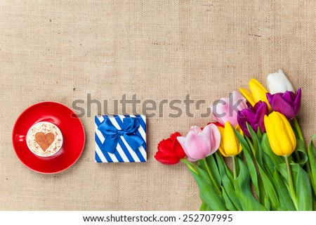 Cup of Cappuccino with heart shape symbol and gift box near flowers on jute background - stock photo