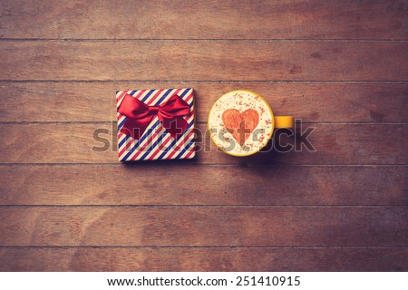 Cup of Cappuccino with heart shape symbol and gift box on wooden background - stock photo