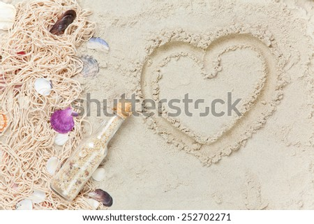Cup of Cappuccino with heart shape symbol and net with shells on sand - stock photo