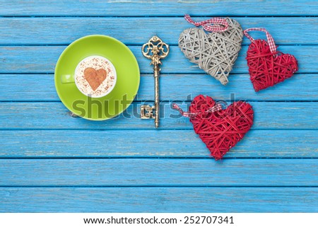 Cup of Cappuccino with heart shape symbol, key and toys on blue wooden background.
