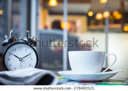 Cup of cappuccino with newspaper and clock on the table, blur coffee shop background  - stock photo