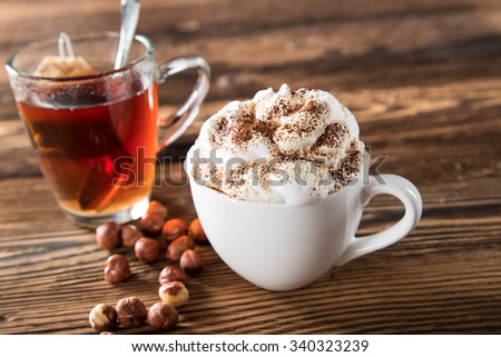Cup Of Cappuccino With Whipeed Cream And Hot Tea Over Wooden Table - stock photo