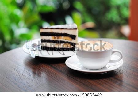 Cup of capuchino coffee with Chocolate Banana Cake. - stock photo