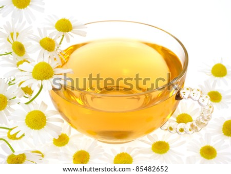 Cup of chamomile tea over white background - stock photo
