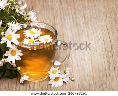 Cup of chamomile tea with chamomile flowers  - stock photo