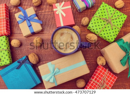 Cup of cocoa and season gifts with leafs on wooden background