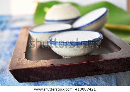 Cup of coconut milk Thai dessert on wooden tray - stock photo