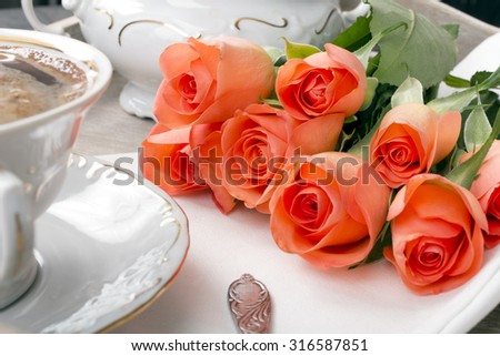 cup of coffee and a bouquet of roses on a tray - stock photo