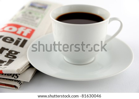 Cup of coffee and a newspaper on a white background - stock photo