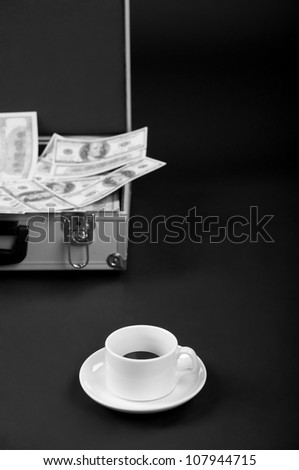cup of coffee and a suitcase of money on a dark background - stock photo