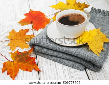 Cup of coffee and autumn leaves on a white wooden table