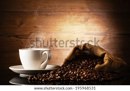 cup of coffee and bag in front of wooden background - stock photo