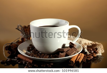 cup of coffee and beans, cinnamon sticks and chocolate on brown background