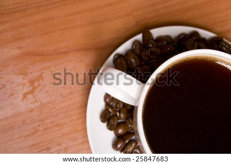 cup of coffee and beans closeup on wooden table