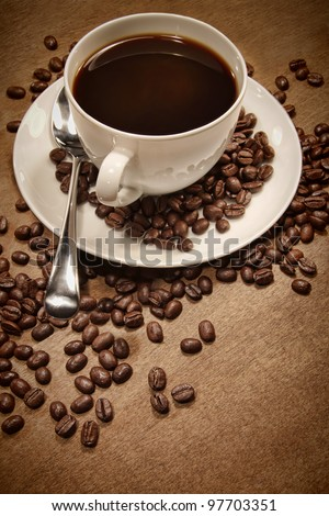 Cup of coffee and beans on wood background - stock photo