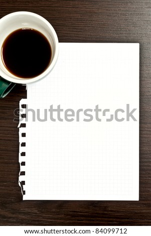 Cup of coffee and blank paper on dark desk - stock photo