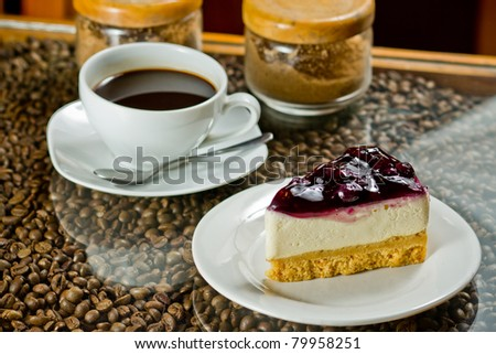cup of coffee and blueberry cake on coffee beans. - stock photo