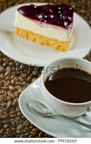 cup of coffee and blueberry cake on coffee beans.