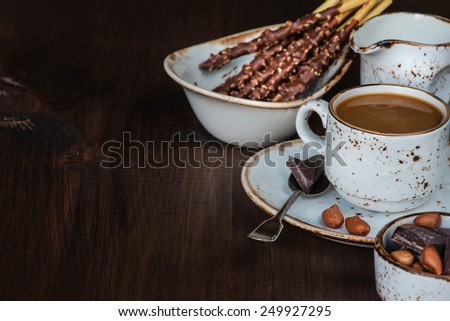 Cup of coffee and bread sticks, chocolate covered with nuts, on dark wooden background - stock photo