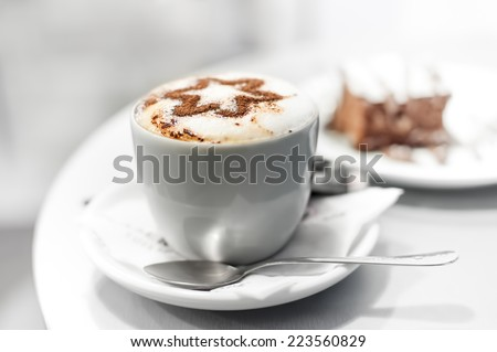 Cup of coffee and cake in cafe, shallow DOF, high key. - stock photo