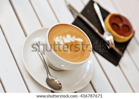 cup of coffee and cake on the wooden background